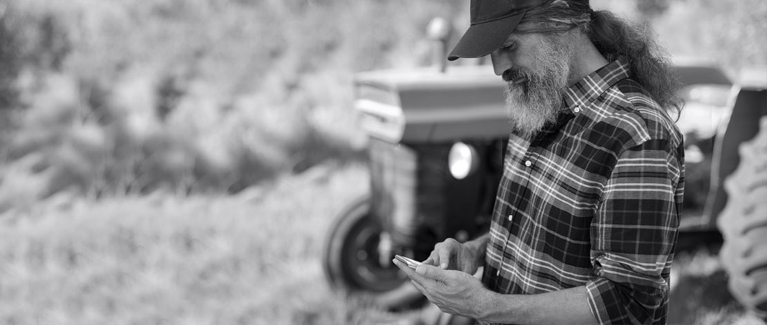 A farmer looking at his phone - Small Talk Big Difference