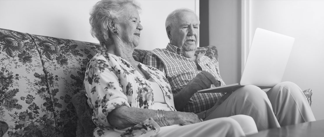 An elderly couple sitting on a couch reading a laptop - Small Talk Big Difference